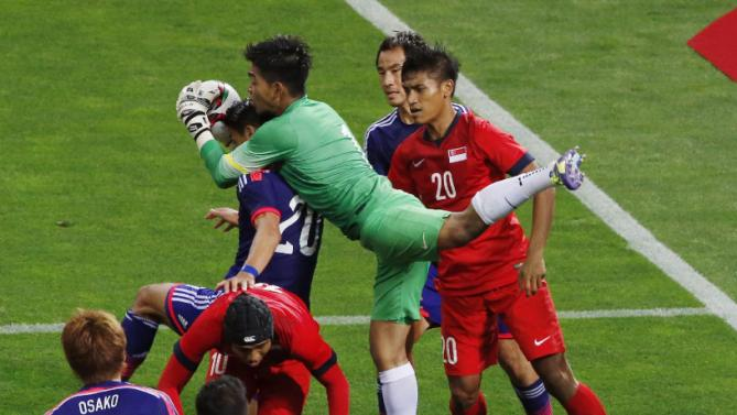 Singapore's goalkeeper Mohamad Izwan Bin Mahbud, center, catches the ball against Japan during their second round soccer match of regional qualifiers for the 2018 World Cup, in Saitama, north of Tokyo, Tuesday, June 16, 2015. The match ended in a 0-0 draw. (AP Photo/Shuji Kajiyama)